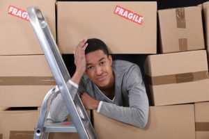 Mark Roemer image of a young man looking frustrated surrounded by boxes.